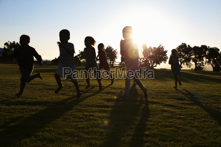 silhouetted elementary school kids running in
