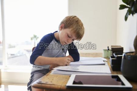 boy sits at desk in bedroom
