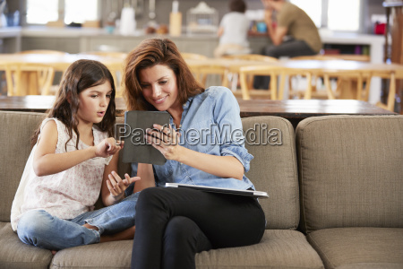 mother and daughter sitting on lounge