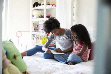 mother and daughter siting on bed