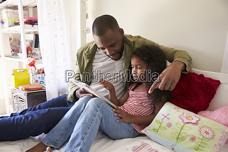 father and daughter siting on bed