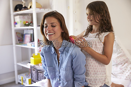 daughter brushes mothers hair as they