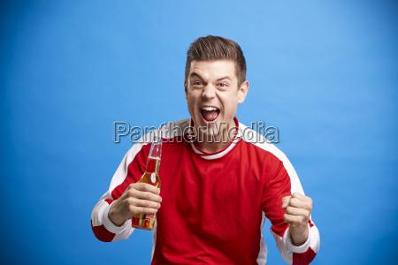 a young male sports fan celebrating