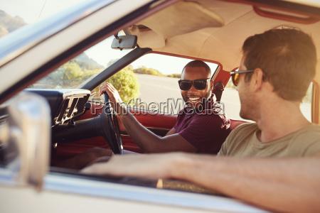 two male friends relaxing in car