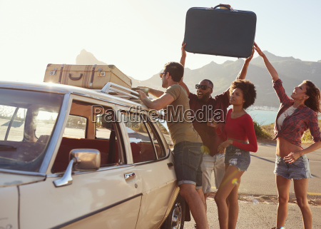 friends loading luggage onto car roof