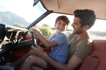 father teaching young son to drive
