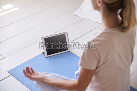 woman with digital tablet using meditation