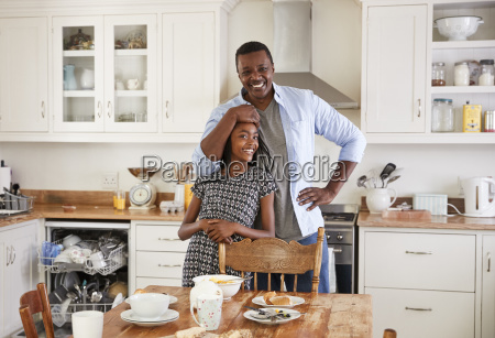 daughter helping father to clear table