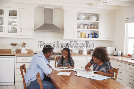 father helping two daughters sitting at