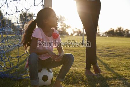 junges maedchen sitzt auf ball neben