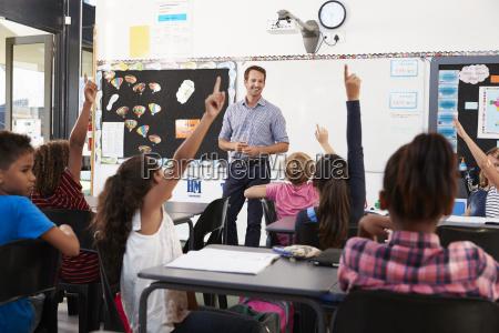 school kids raising hands in elementary