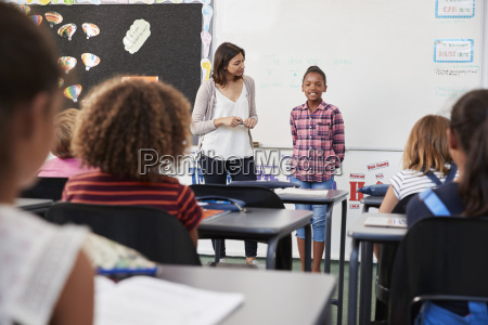 teacher and pupil stand at front