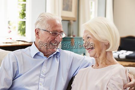 smiling senior couple sitting on sofa