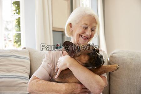 senior woman sitzt auf sofa zu