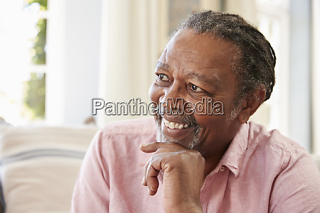 smiling senior man sitting on sofa