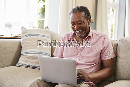 senior man sitting on sofa using