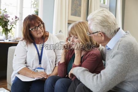 support worker visits senior woman suffering