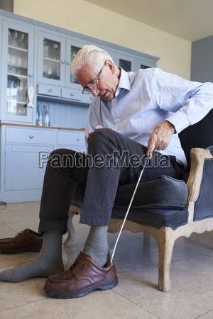 senior man in chair using aid