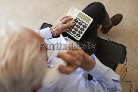 senior man at home using telephone