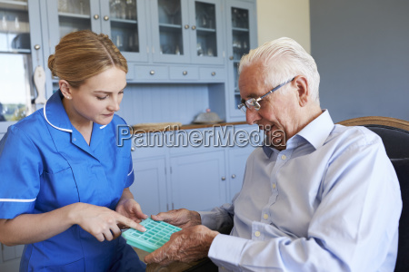 krankenschwester hilft leitenden mann medikamente auf
