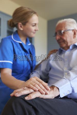 community nurse visits senior man suffering