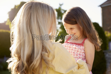 mother hugging daughter outdoors in summer