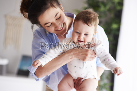 happy mother carrying her baby at