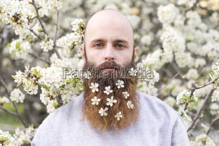 portraet von hipster mit weissen baumblueten