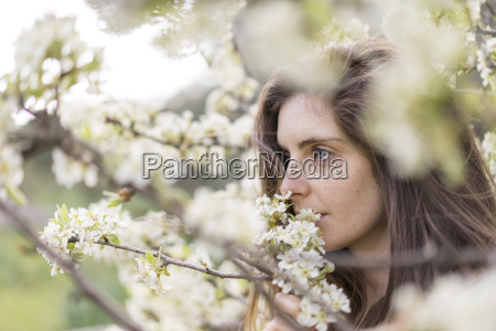 woman smelling white blossoms of fruit