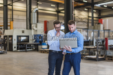 two businessmen sharing laptop on factory