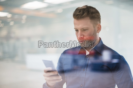 businessman looking on cell phone behind