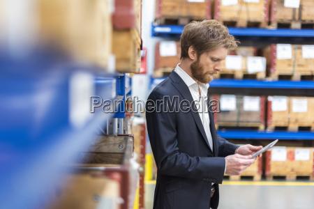 geschaeftsmann der tablette im fabriklagerraum verwendet