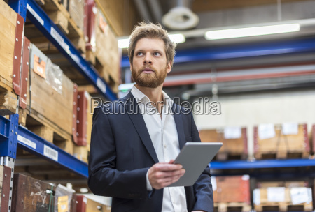 businessman with tablet in factory storeroom