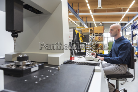 man using computer at machine in
