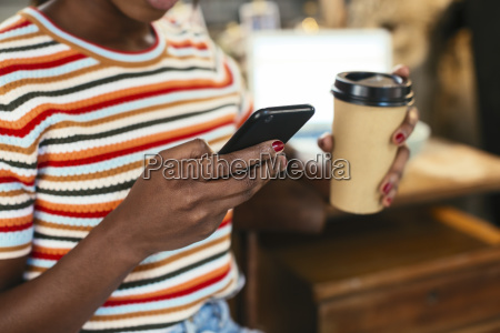 woman holding coffee to go while