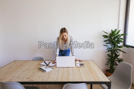 junge geschaeftsfrau am schreibtisch mit laptop