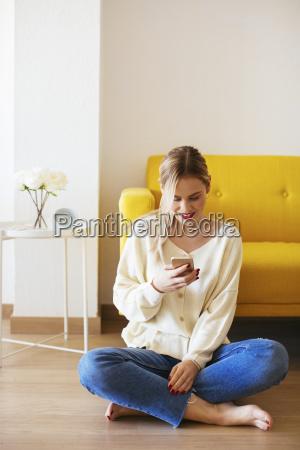 blonde frau mit smartphone zu hause