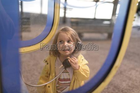 portrait of little girl using telephone