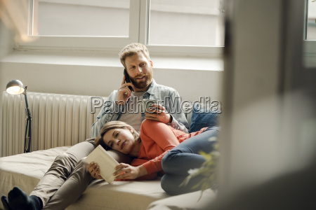 happy couple reading and cuddling at