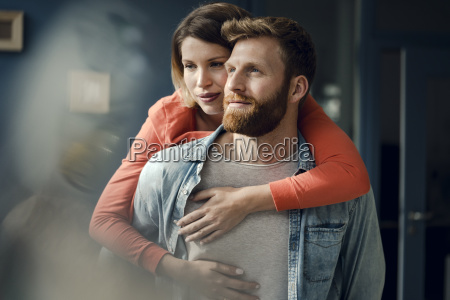 happy couple embracing at home