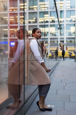 smiling businesswoman leaning against glass pane
