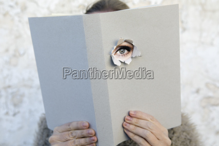 woman covering face with book reading