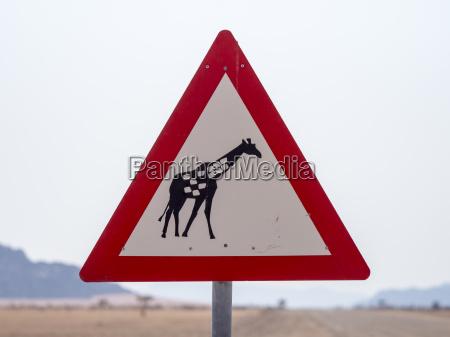 afrikanamibiaverkehrsschildvorsicht etikettgiraffe