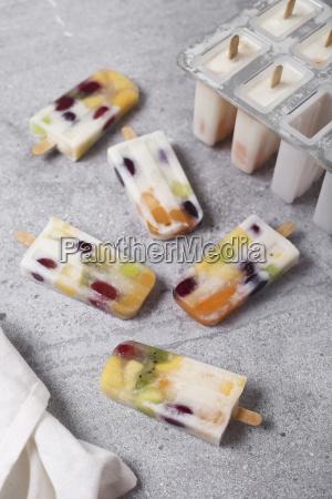 hausgemachte fruechte und joghurteis auf marmor