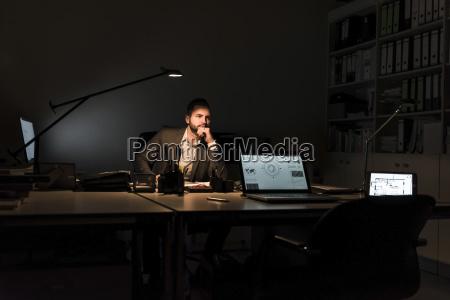 pensive businessman sitting at desk in