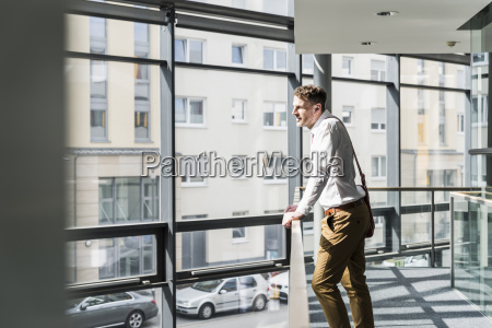 businessman standing in office building leaning
