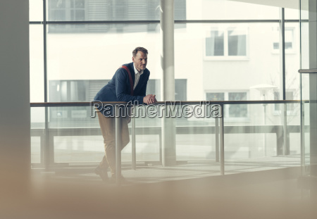 businessman in office building leaning on