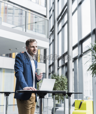 smiling businessman with cup of coffee