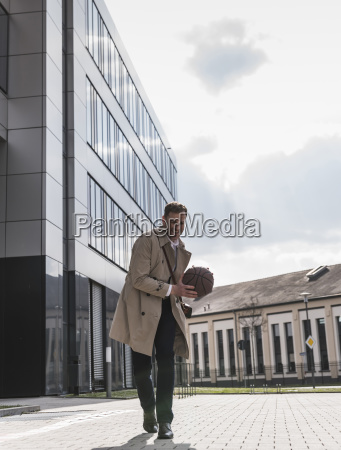 happy businessman playing basketball outside office