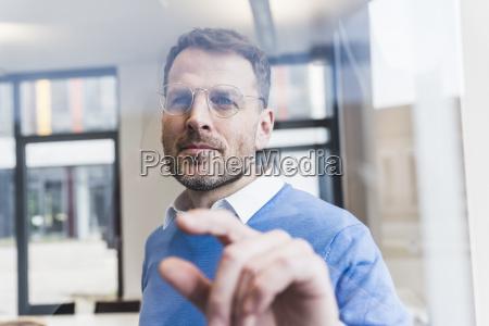 confident businessman touching glass pane